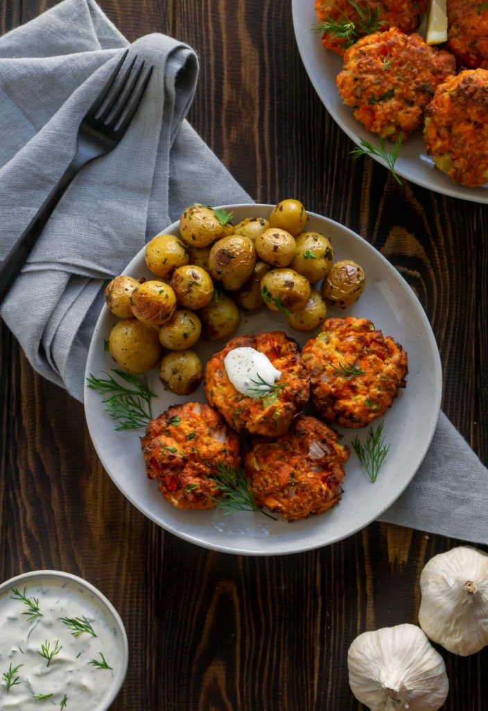 salmon cakes on a plate with potatoes, garlic and lemon dill sauce to the side