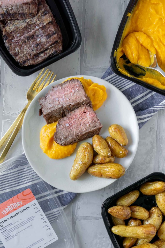 a la carte territory with steak, butternut squash mash, and potatoes on a white plate