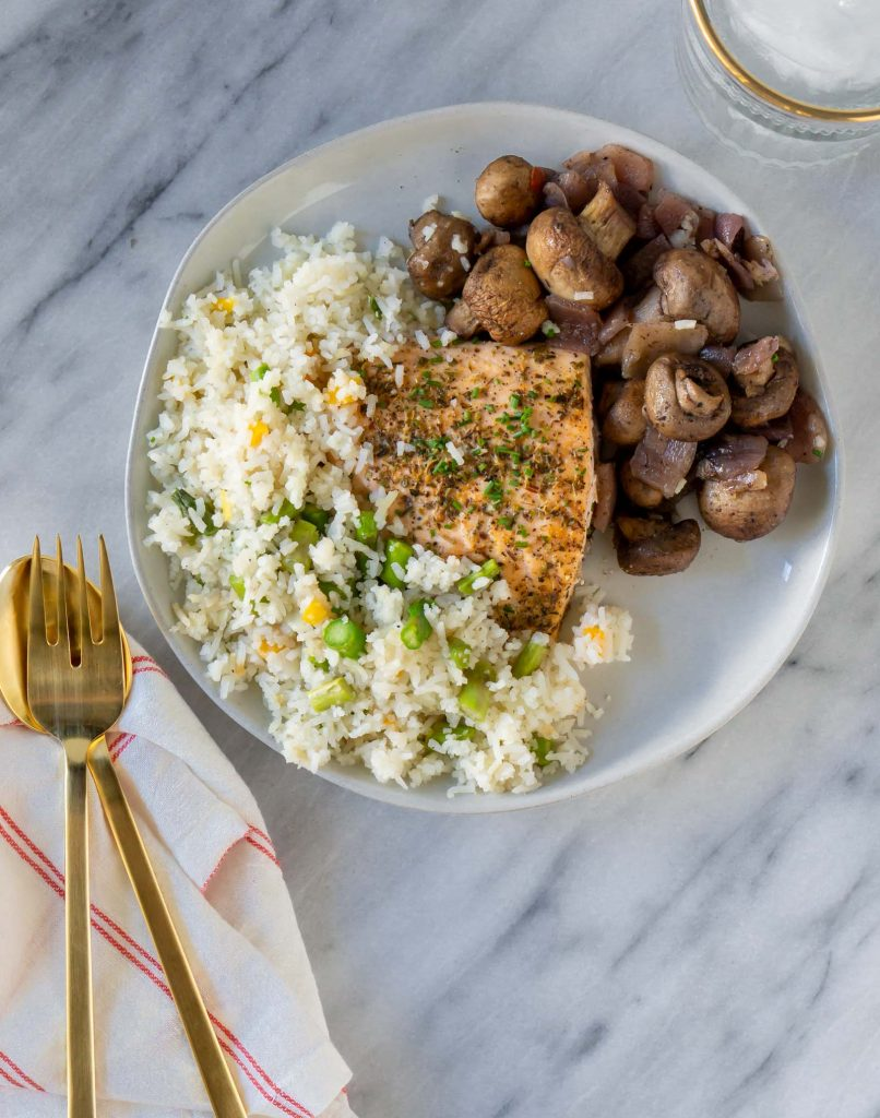 salmon, rice, and mushrooms on a plate with a gold fork