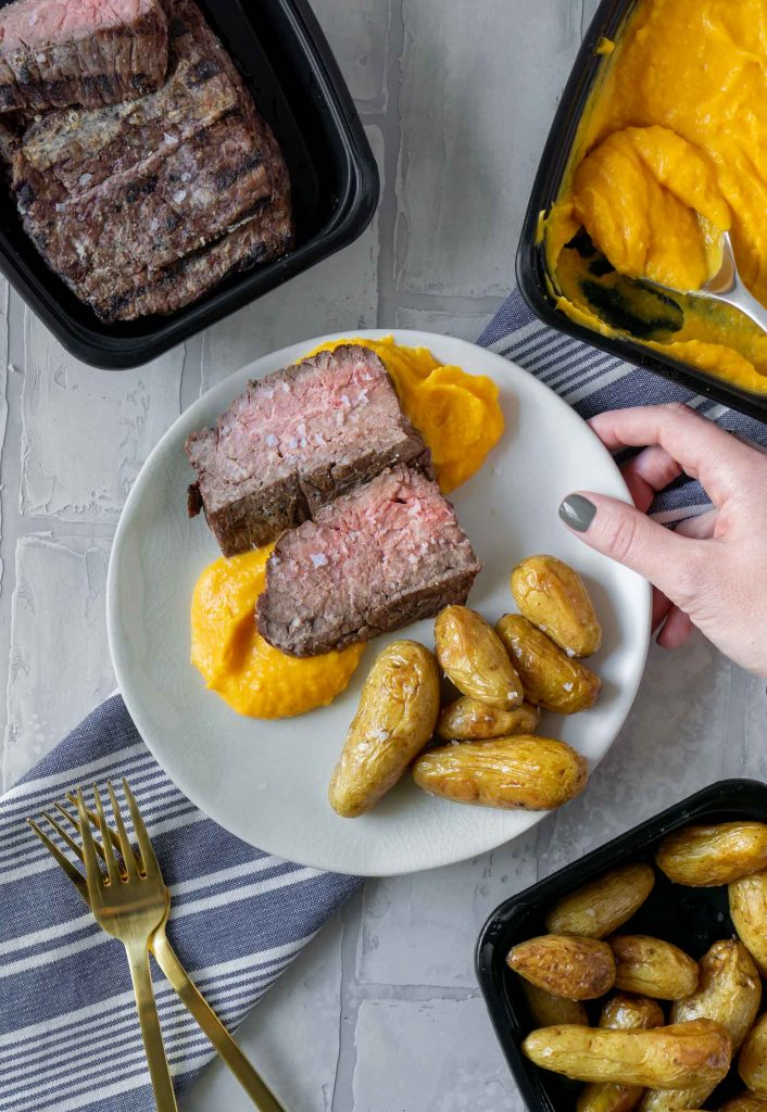 steak, butternut squash mash, and potatoes on a white plate
