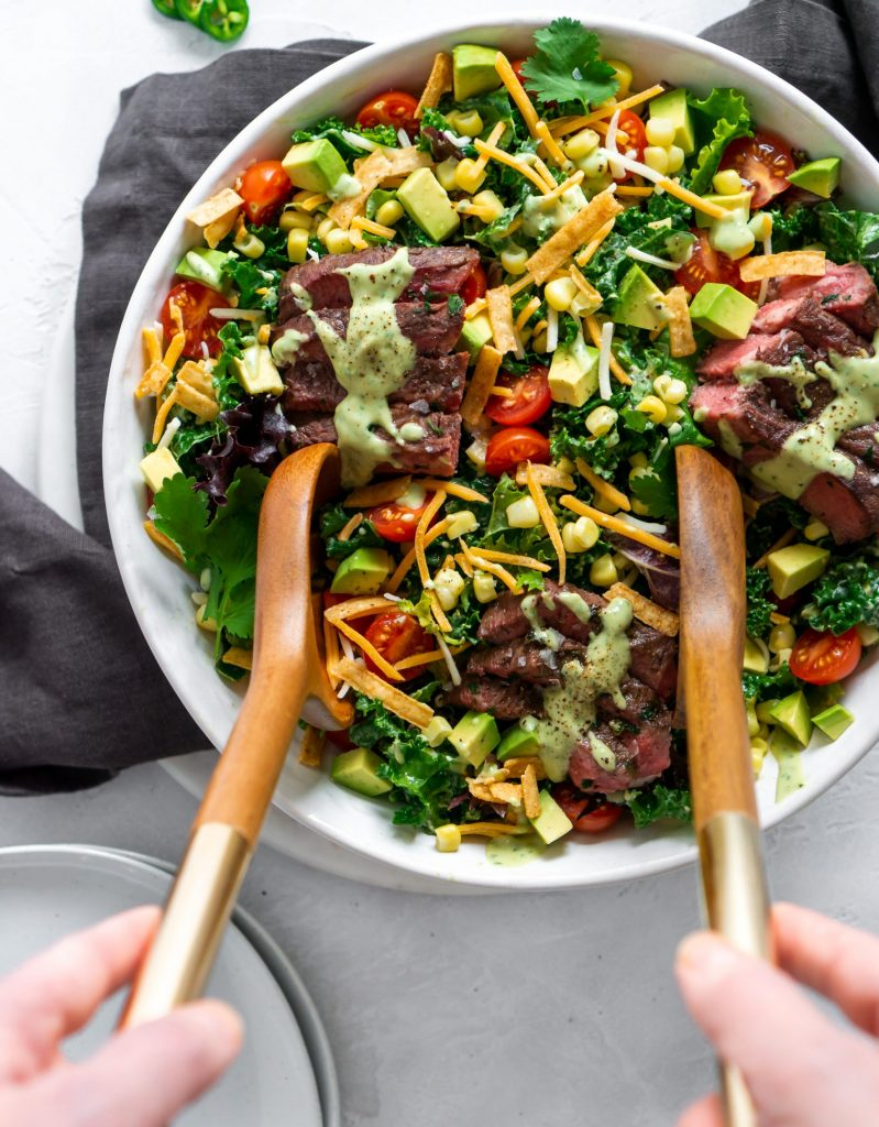 two hands holding salad tongs to serve
