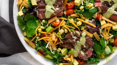 tex mex flank steak salad in a large white bowl