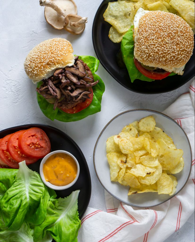 two burgers, chips on a white plate, lettuce and tomato on a black plate