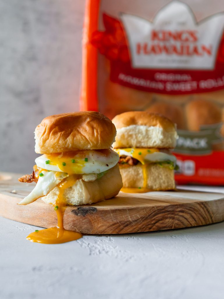two breakfast sandwich sliders on a wood serving board