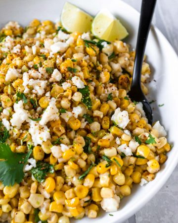 mexican street corn dip in a white bowl with a black fork