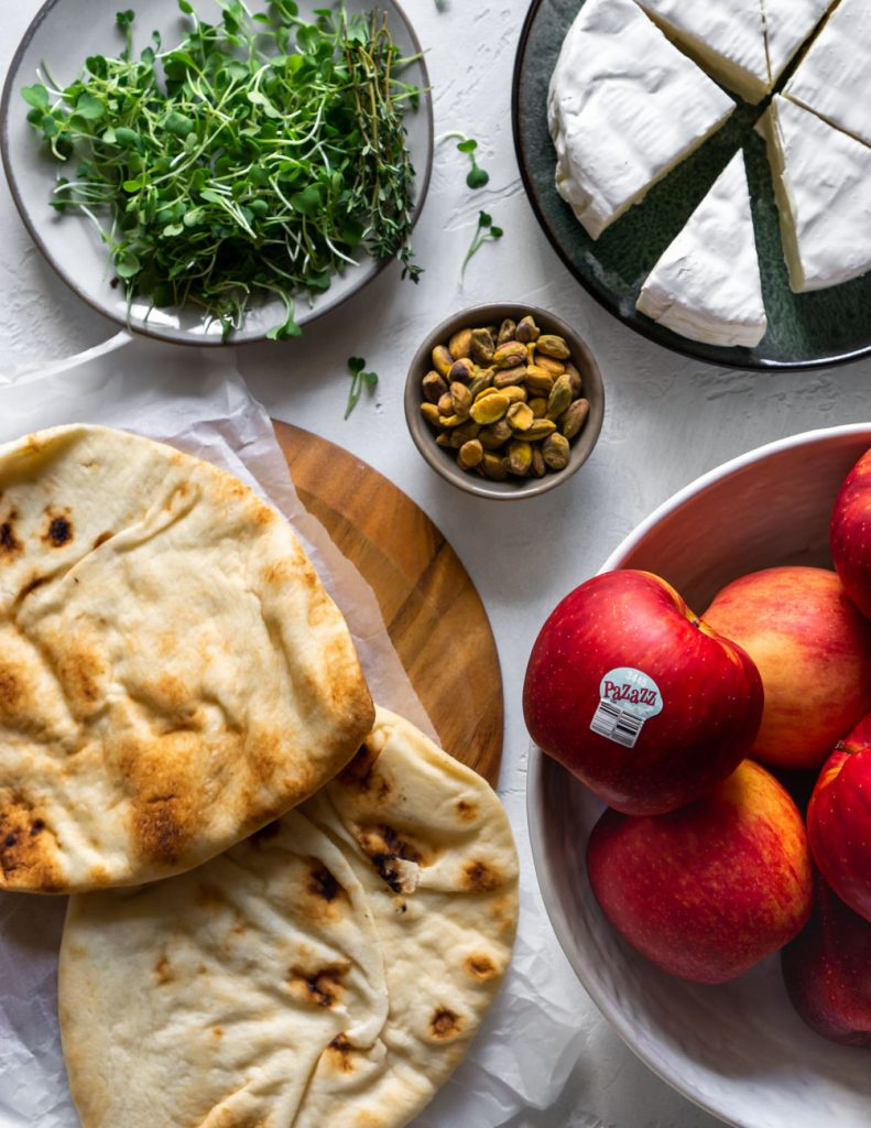 ingredients for baked brie flatbread pizza, apples, naan, pistachios