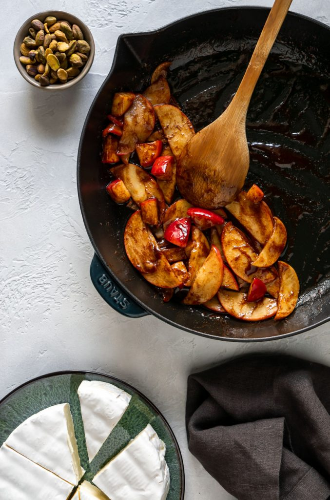 cinnamon glazed apples in a skillet with a wooden spoon