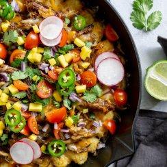 slow cooker carnitas tater tot nachos in a skillet