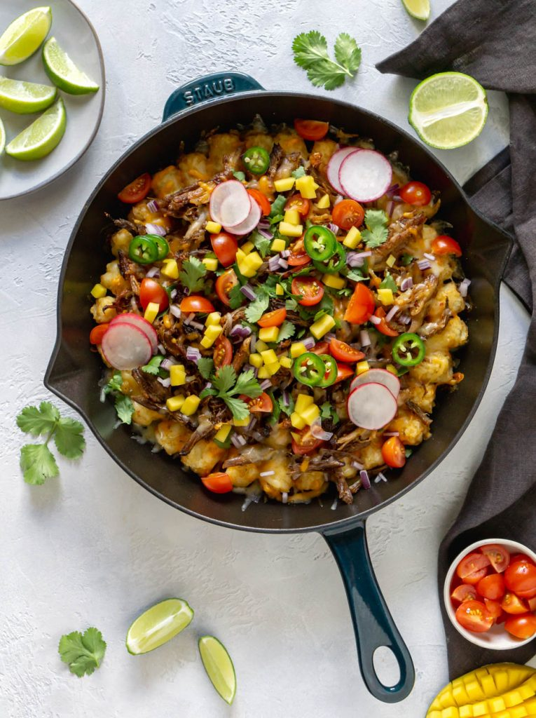 carnitas totchos in a skillet with limes, tomatoes, and a napkin