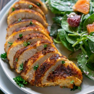 sliced air fryer chicken on a white plate with salad