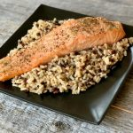 salmon over rice on a black plate