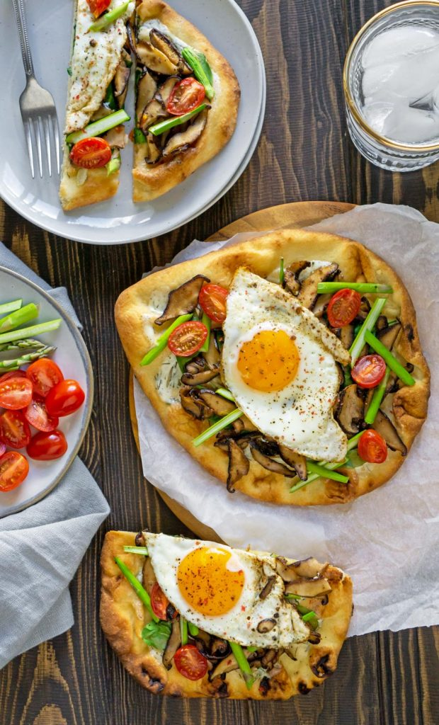 breakfast pizza on parchment paper and on a plate with a glass of water