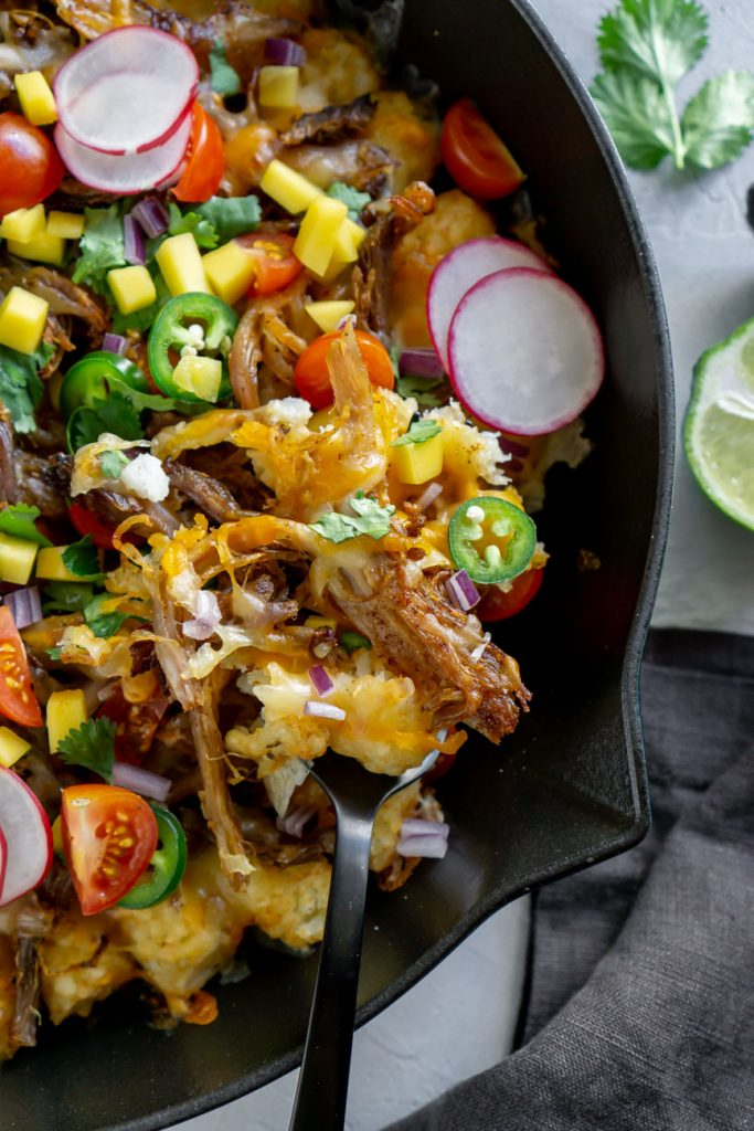 tater tot nachos in a cast iron skillet