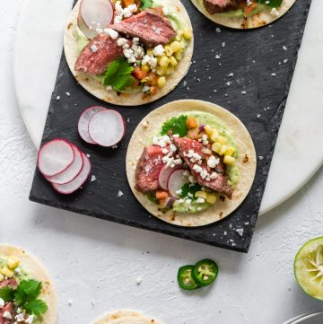 three steak tacos on a black slate board