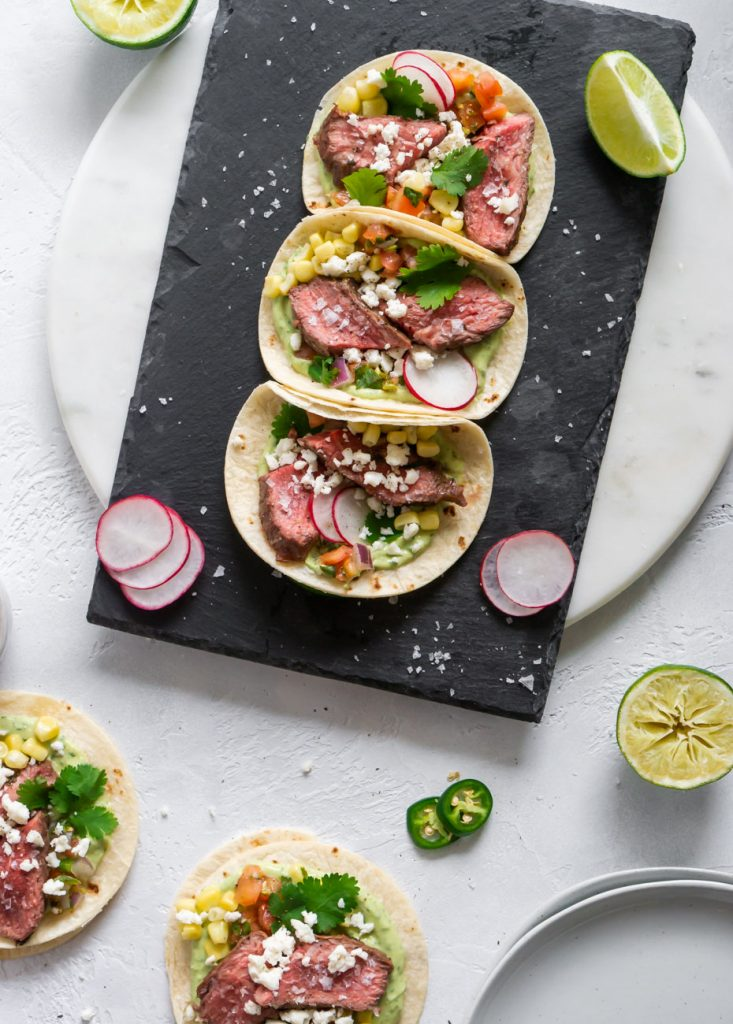 five steak tacos on a marble board with plates and limes