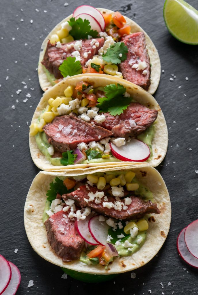 close up of steak tacos on a black slate board