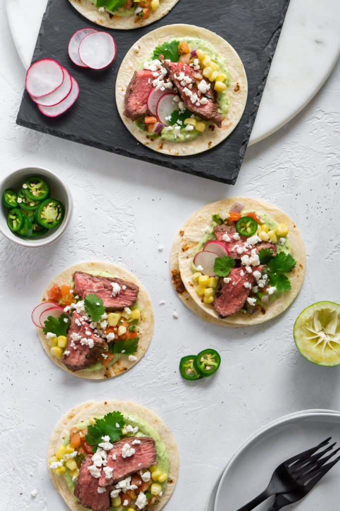 four steak tacos, a plate with black forks, and sliced jalapenos