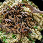 mushroom risotto in a skillet with a wooden spoon