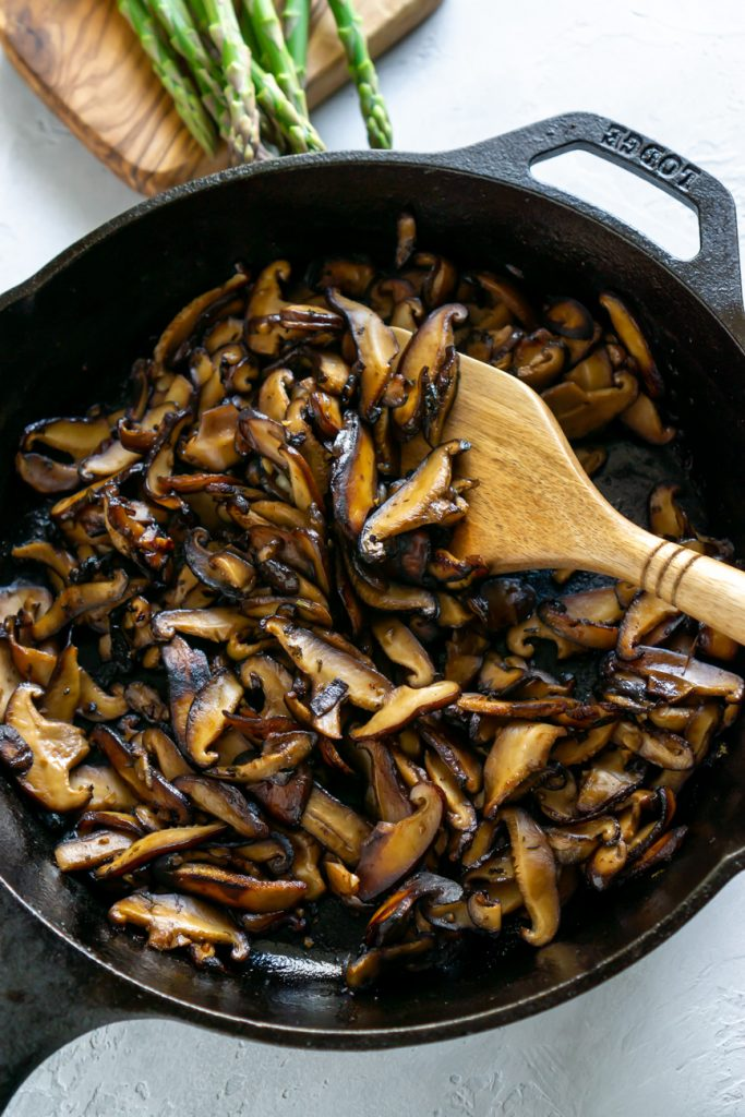 balsamic mushrooms in a pan with wooden spoon