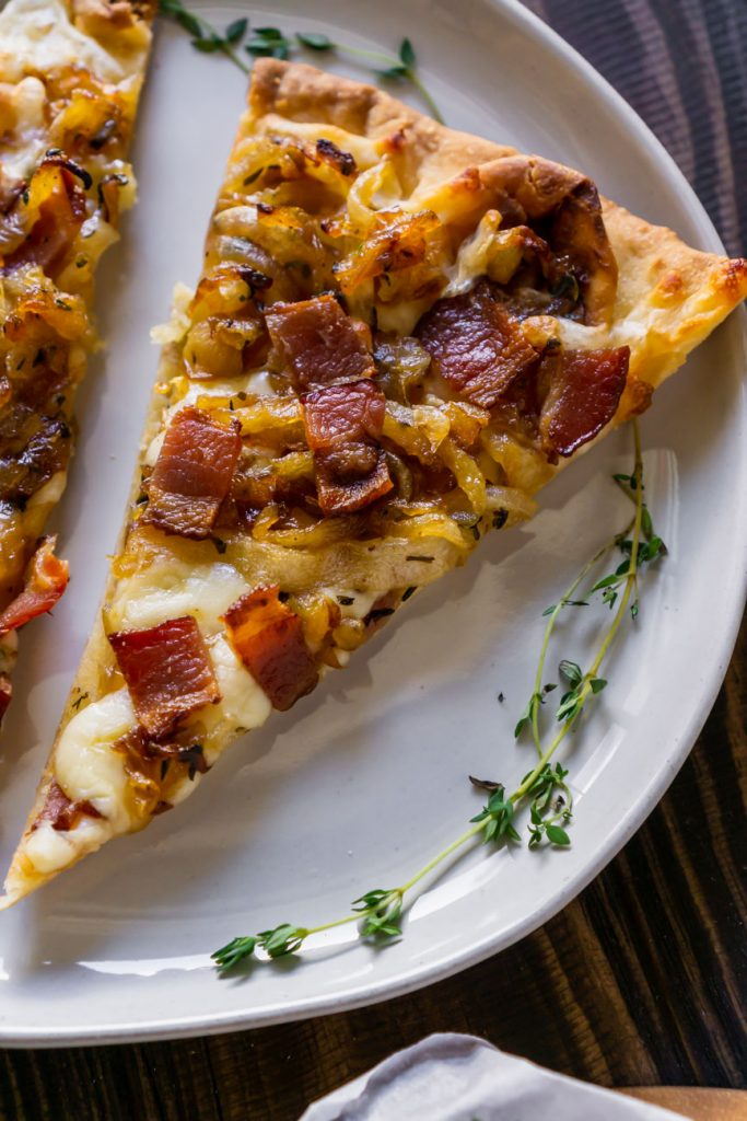 a slice of bacon pizza on a white plate