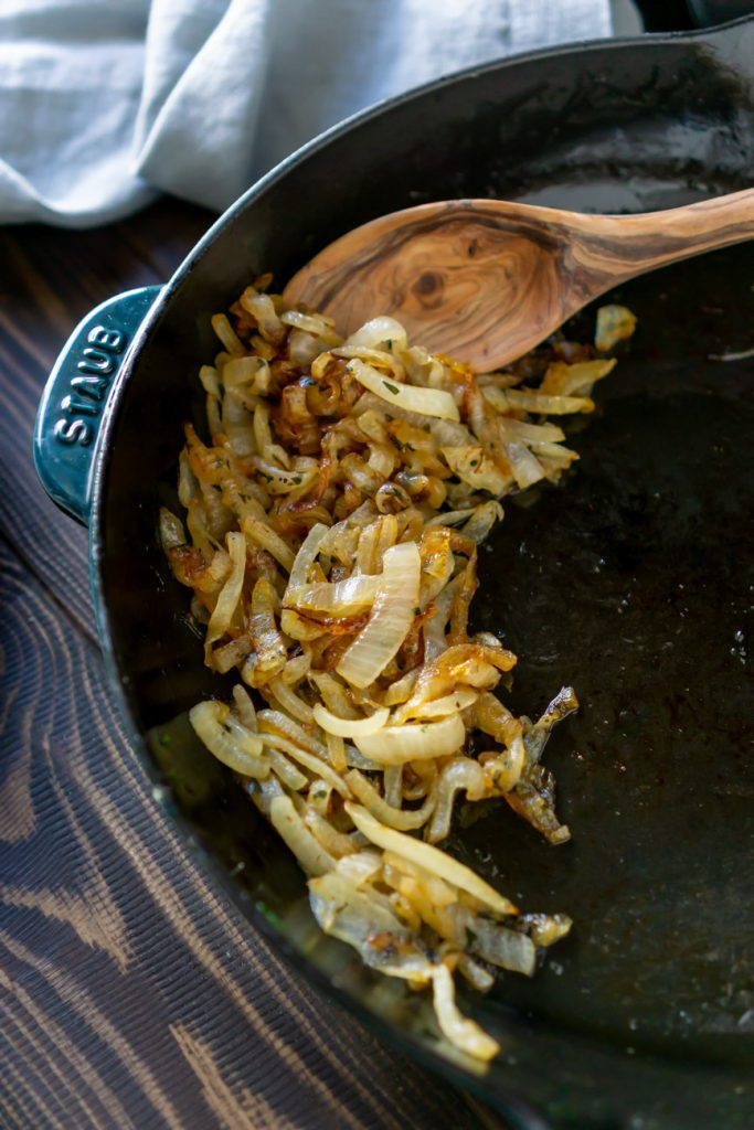 caramelized onions in a skillet with a wooden spoon
