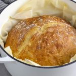 no knead artisan bread in a large white pot with parchment paper