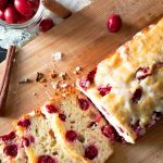 cranberry orange bread sliced on a wood board with cranberries around