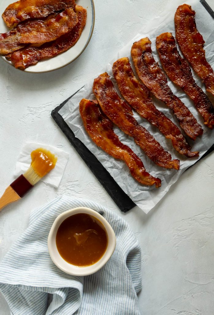 maple miso glaze in a white bowl with a pastry brush and bacon on parchment paper