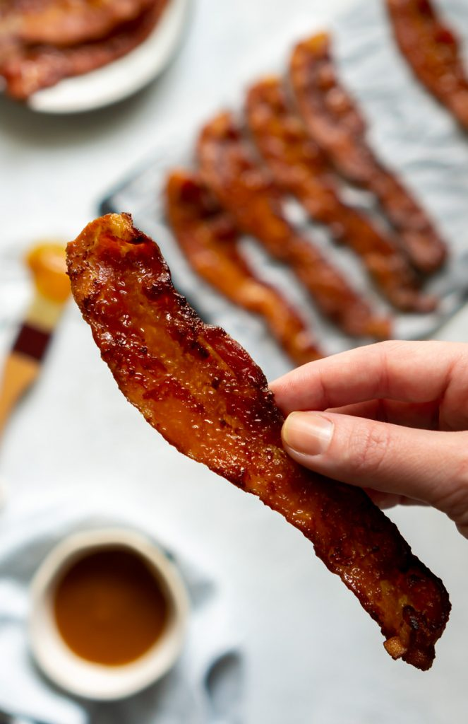 a hand holding a strip of candied bacon