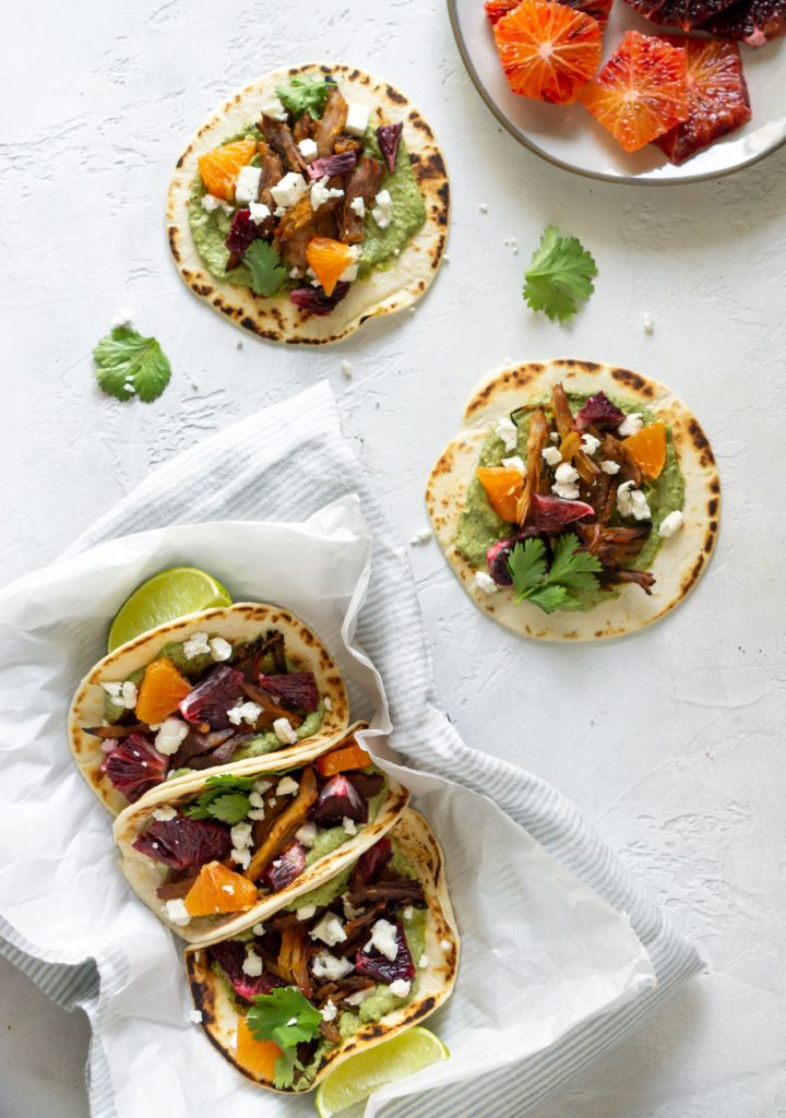 three tacos on parchment paper, two tacos on a white background, and blood oranges on a plate