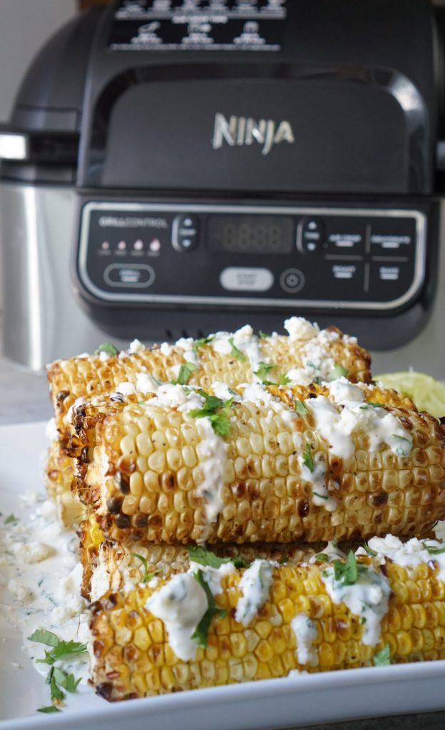 corn on a white plate and an air fryer