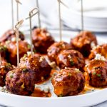 buffalo chicken meatballs on a white plate with toothpicks