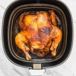 air fryer whole roasted chicken in an air fryer basket