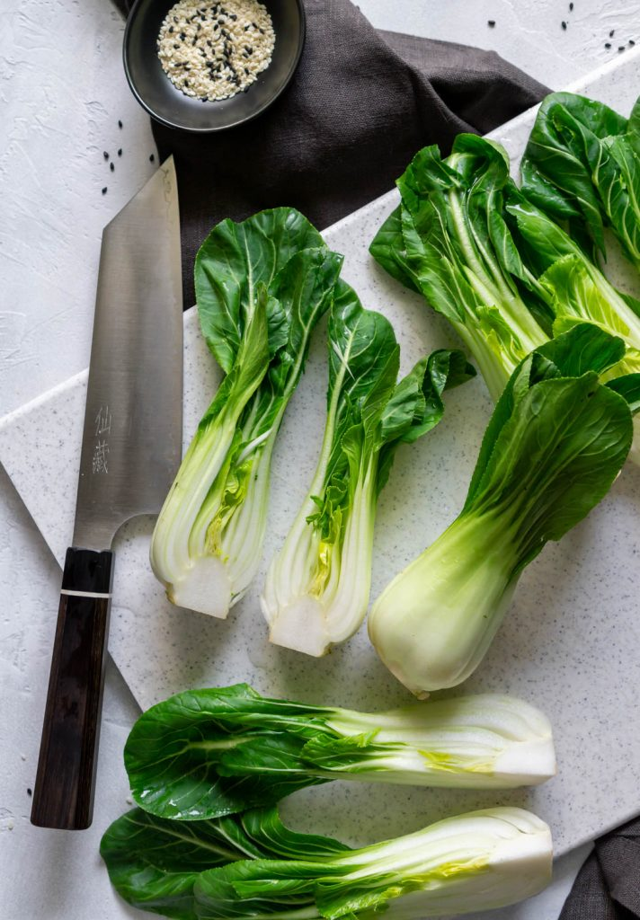 bok choy on a white cutting board with a knife