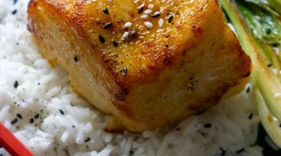miso glazed chilean sea bass on a black plate with rice and red chopsticks