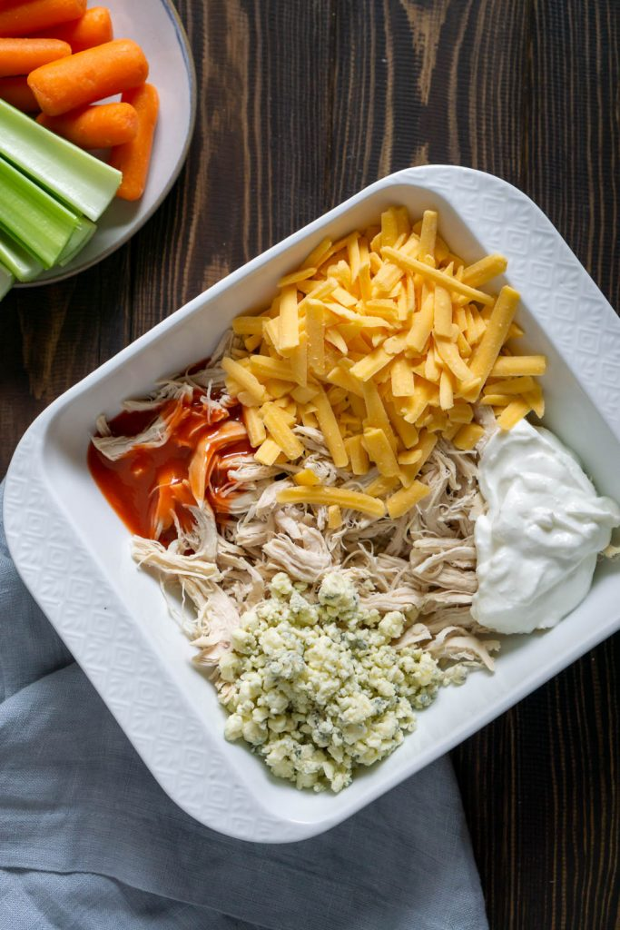 skinny buffalo chicken dip ingredients in a white baking dish