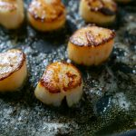 seared scallops in a black skillet