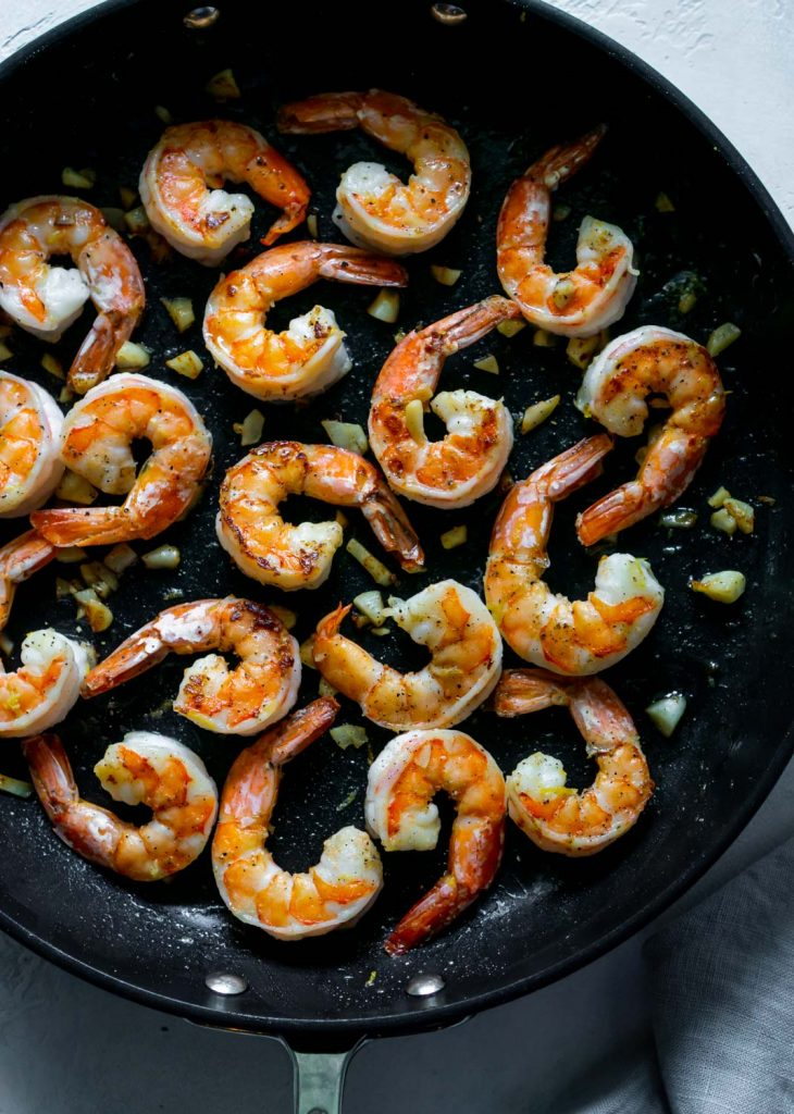 garlic butter shrimp in a large black pan