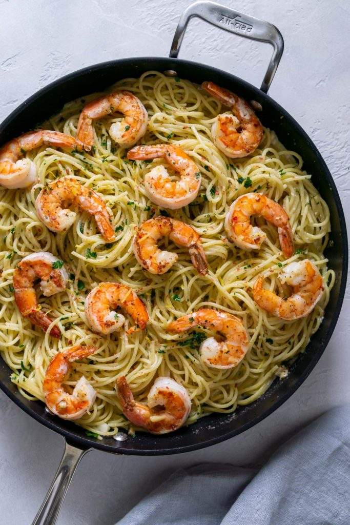 pasta in a large black pan with jumbo shrimp on top