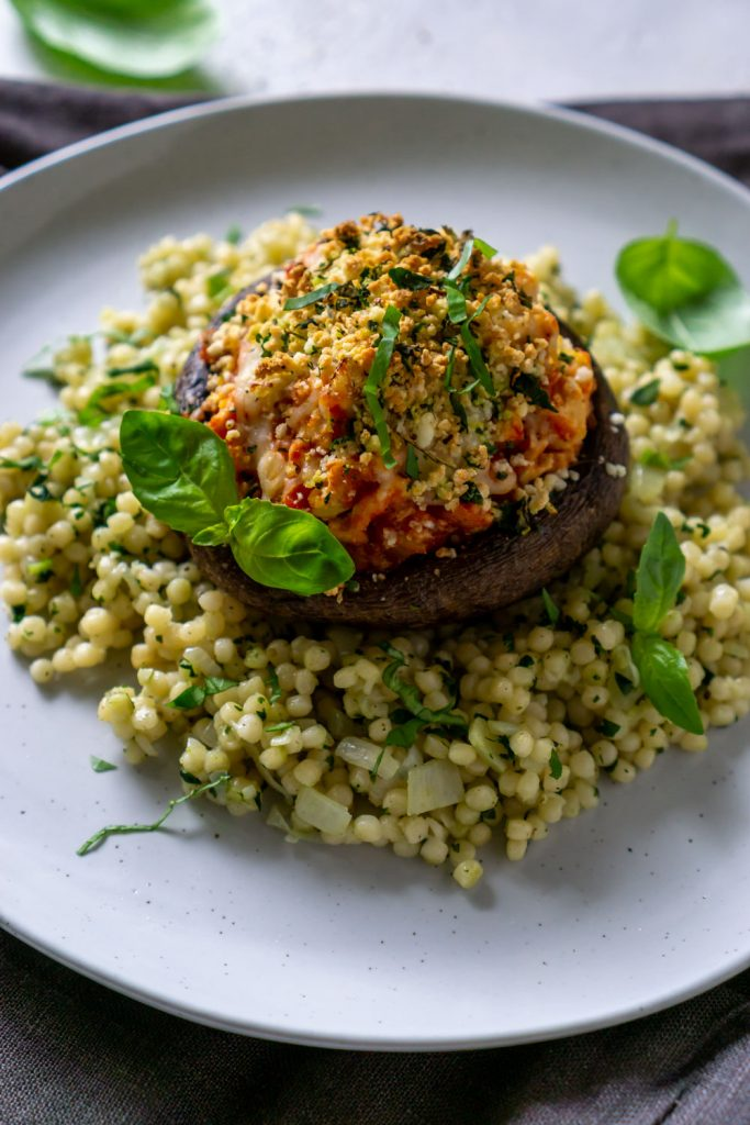 air fryer stuffed mushroom on a white plate with couscous