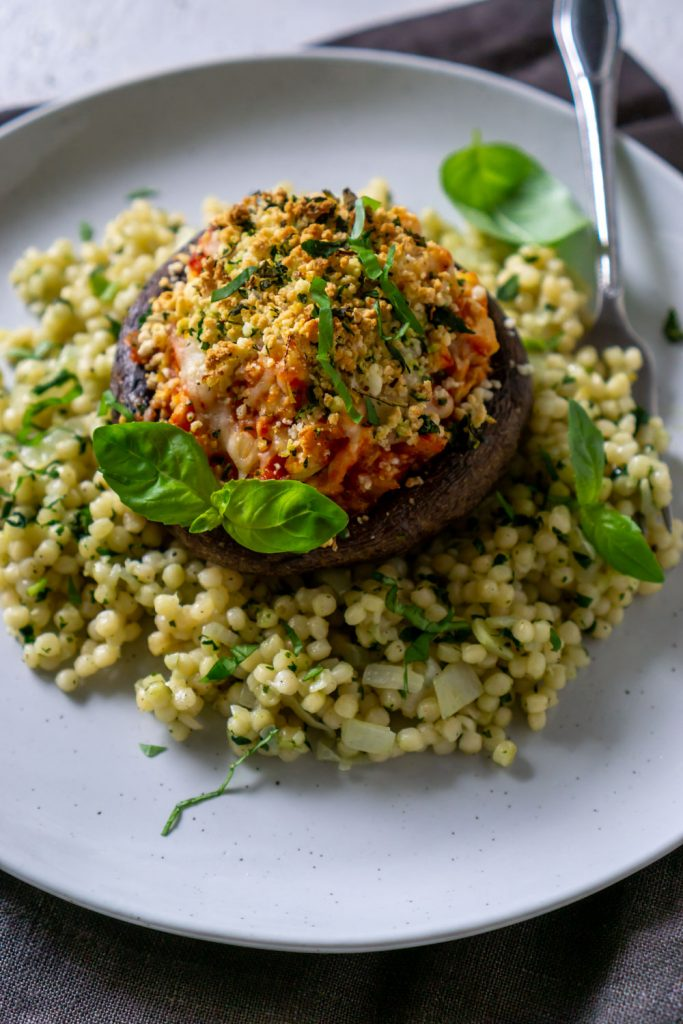 chicken parmesan stuffed mushrooms on a plate with couscous and a fork