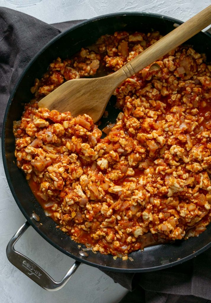 ground chicken with marinara sauce in a black pan with wooden spoon