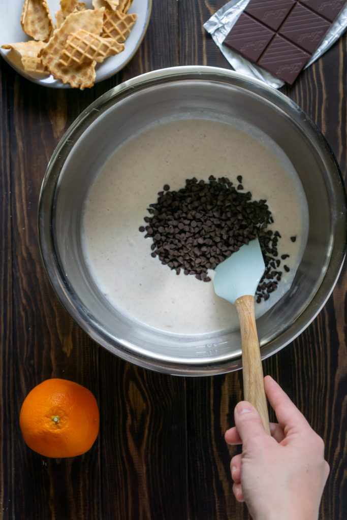 spatula mixing chocolate chips into cannoli dip