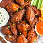 air fryer buffalo wings with celery on a white plate