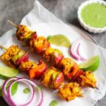 chicken tikka on skewers with lime wedges and red onion slices