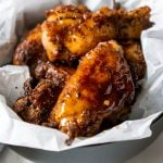 honey old bay wings in a black bowl with white parchment paper