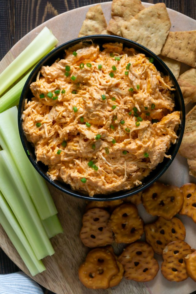 slow cooker buffalo chicken dip in a black bowl with celery and pretzels