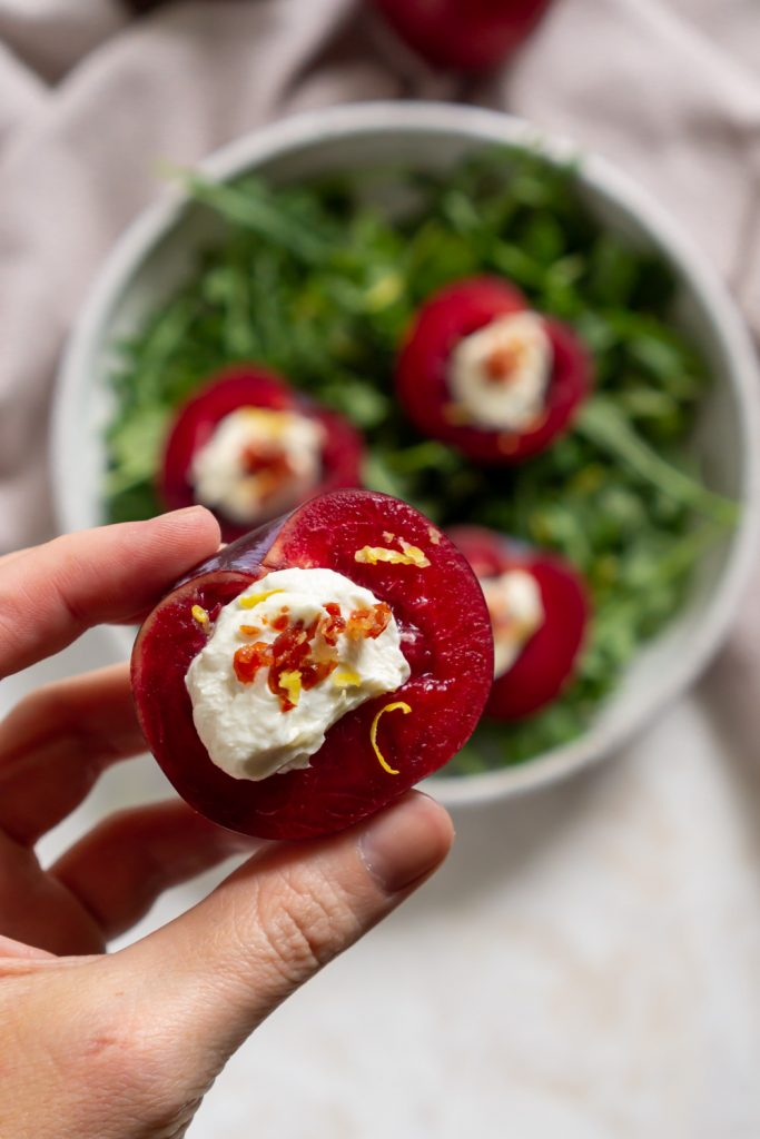 hand holding a whipped goat cheese stuffed plum
