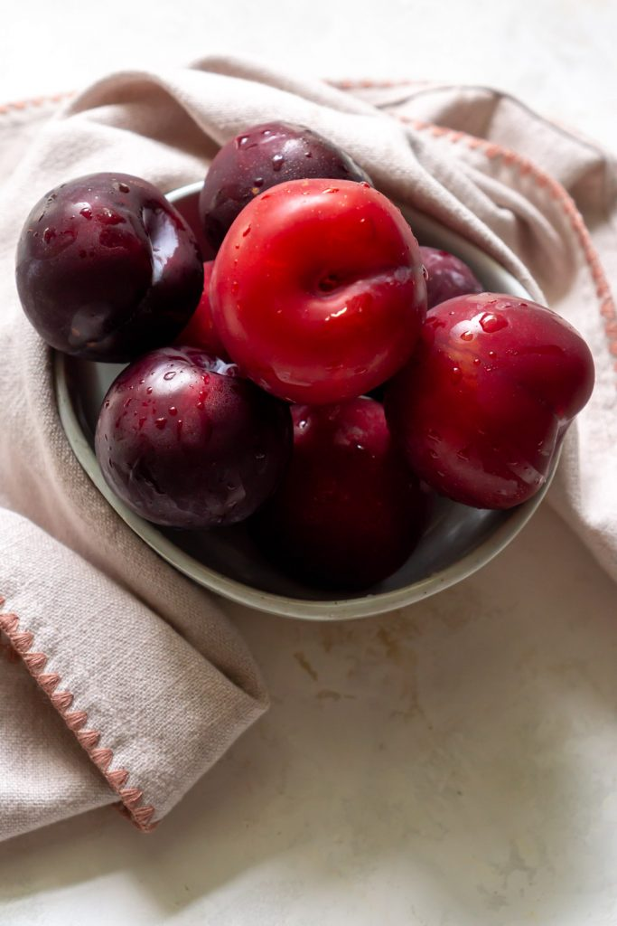 plums in a bowl with a pink napkin