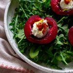 stuffed plums over arugula in a white bowl